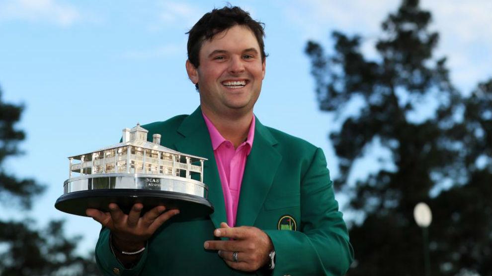 Patrick Reed posa con el trofeo de campeón vestido con la chaqueta...