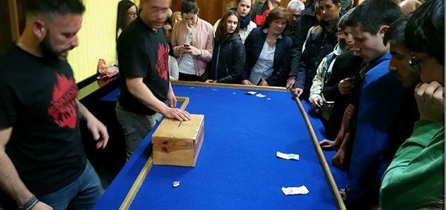 Varios jugadores se reúnen en torno a una mesa para jugar