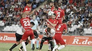 Tino Costa y Morcillo, de espaldas, en una barrera durante el partido...