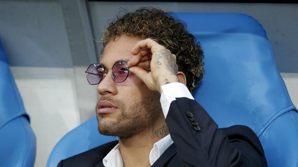 Neymar se ajusta las gafas de sol sentado en un banquillo.