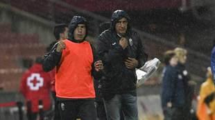 Portugal y su ayudante, bajo la lluvia durante su primer partido en...