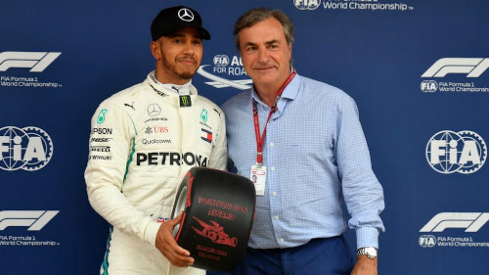Carlos Sainz, entregando la rueda conmemorativa a Hamilton por la pole