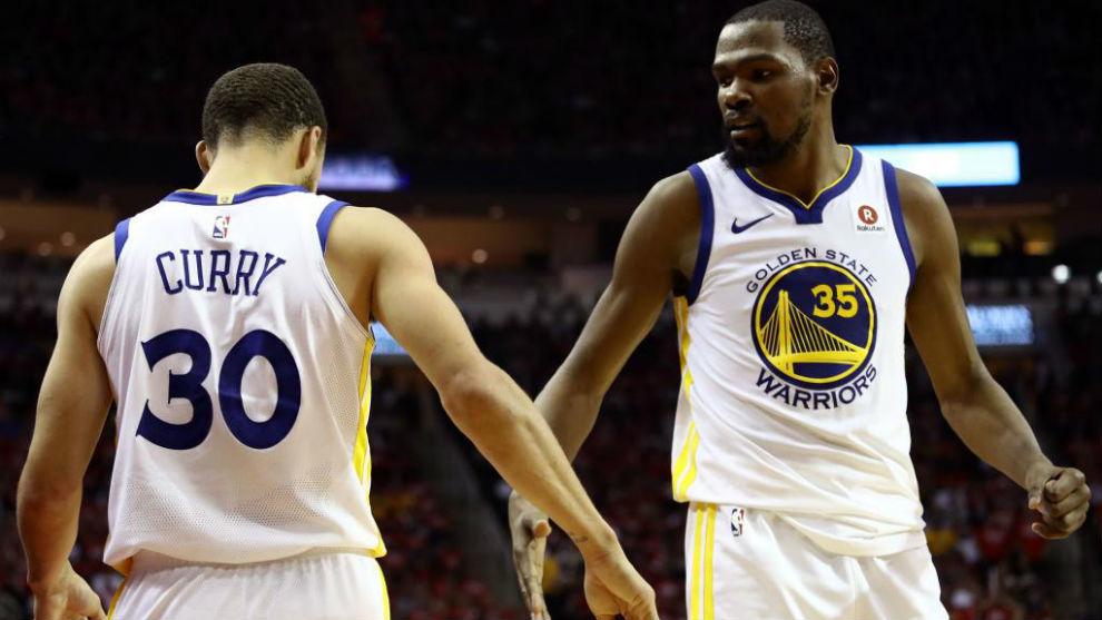 Stephen Curry y Kevin Durant se saludan durante el primer partido...