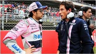 Checo Pérez habla con un miembro de su equipo en una carrera.