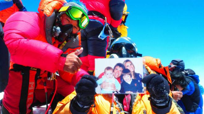 Javier Camacho, en la cima del Everest, con la foto de su familia.