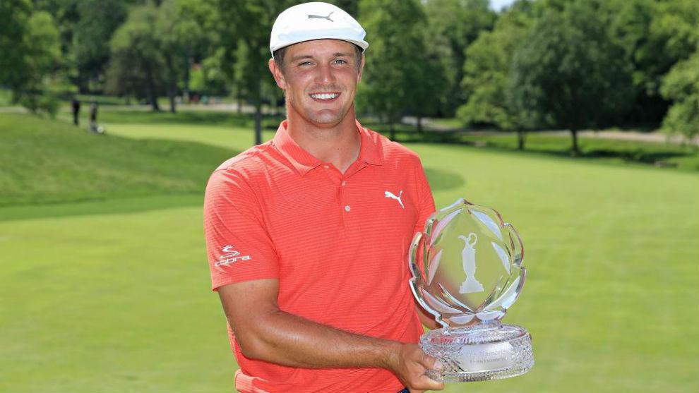 Bryson DeChambeau posa con el trofeo de ganador del Memorial...