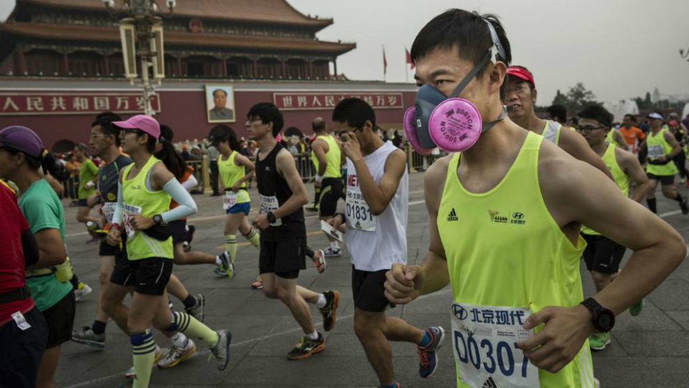 Varios corredores disputan el maratón de Pekín con mascarillas para...