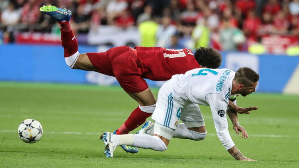 Salah y Sergio Ramos pugnan por un balón