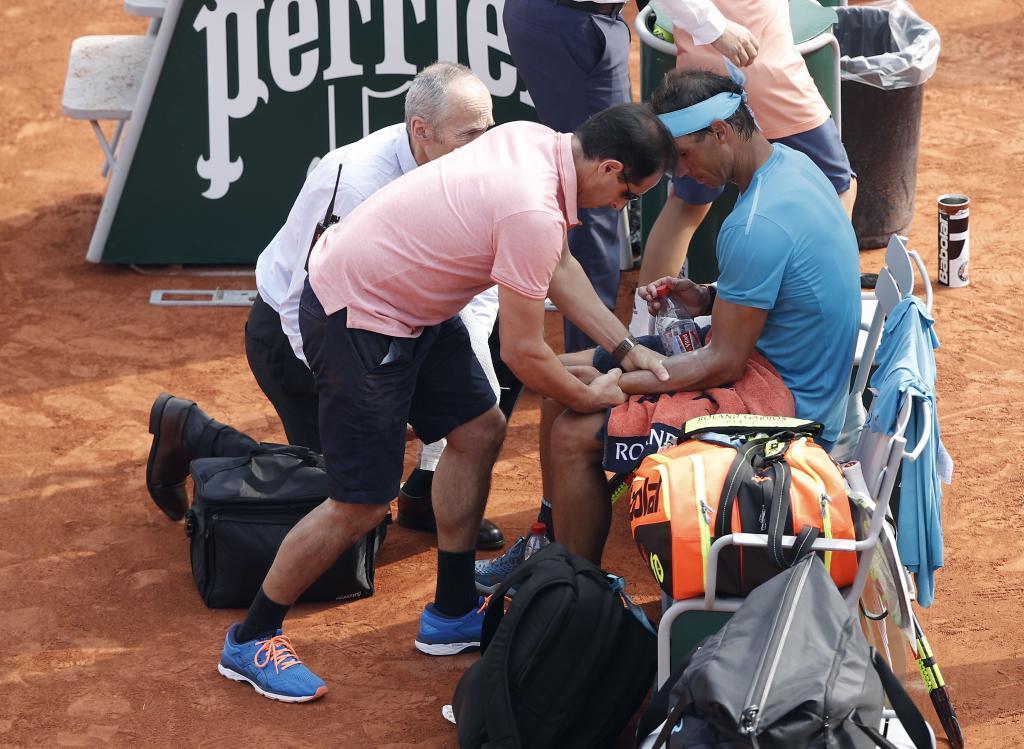 Nadal es atendido de los calambres en la final de Roland Garros.
