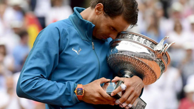 Rafael Nadal of Spain celebrates with the trophy after winning his...