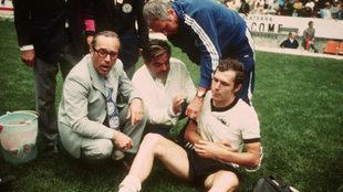 Beckenbauer, con el hombro derecho maltrecho, recibe las atenciones de...