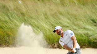 Dustin Johnson of the United States plays a shot from a bunker on the...