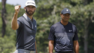 Dustin Johnson of the US (L) reacts in front of Tiger Woods of the US...