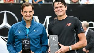 Federer y Raonic, con los trofeos