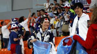 Aficionados japoneses recogiendo la basura tras el partido.