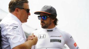 Zak Brown y Fernando Alonso se estrechan la mano.