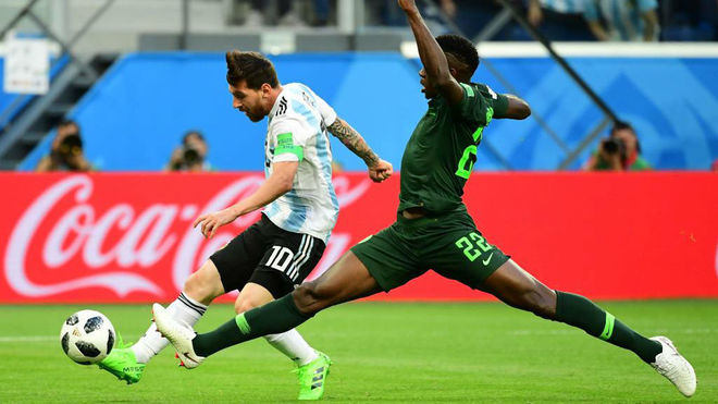 Leo Messi shoots score as he is marked by Omeruo during the match...