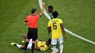 El colegiado Milorad Mazic muestra una amarilla al senegalés Mbaye...