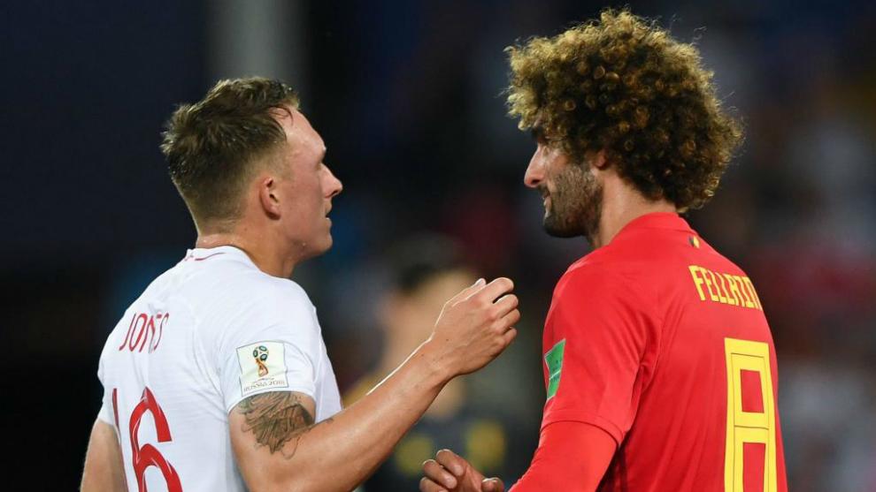 England's defender Phil Jones (L) talks with Belgium's midfielder...