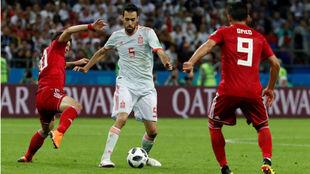 Busquets controla la pelota ante dos jugadores de Irán.