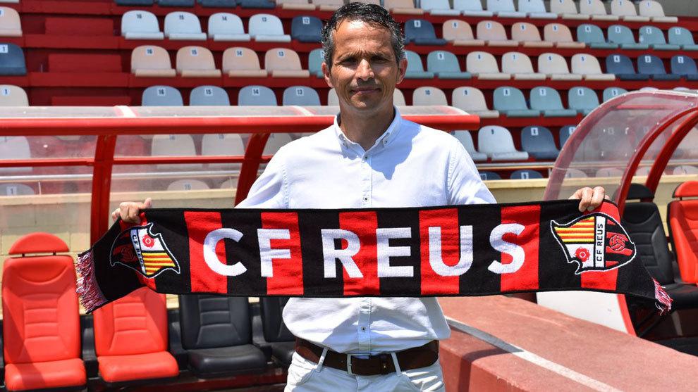 El nuevo entrenador rojinegro posando con una bufanda del club.