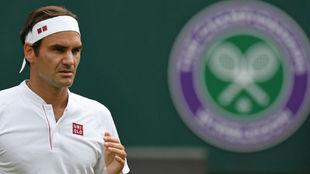 Federer, al lado del escudo de Wimbledon