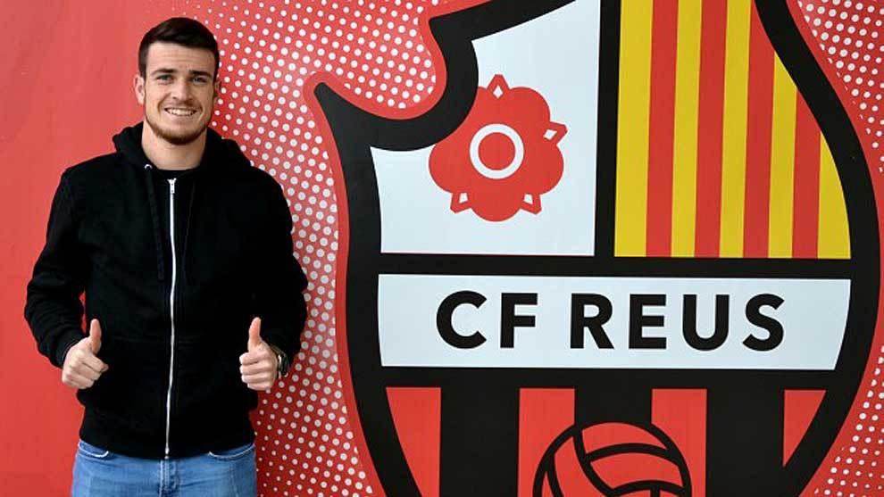 Adrián Guerrero, posa sonriente delante del escudo de su club