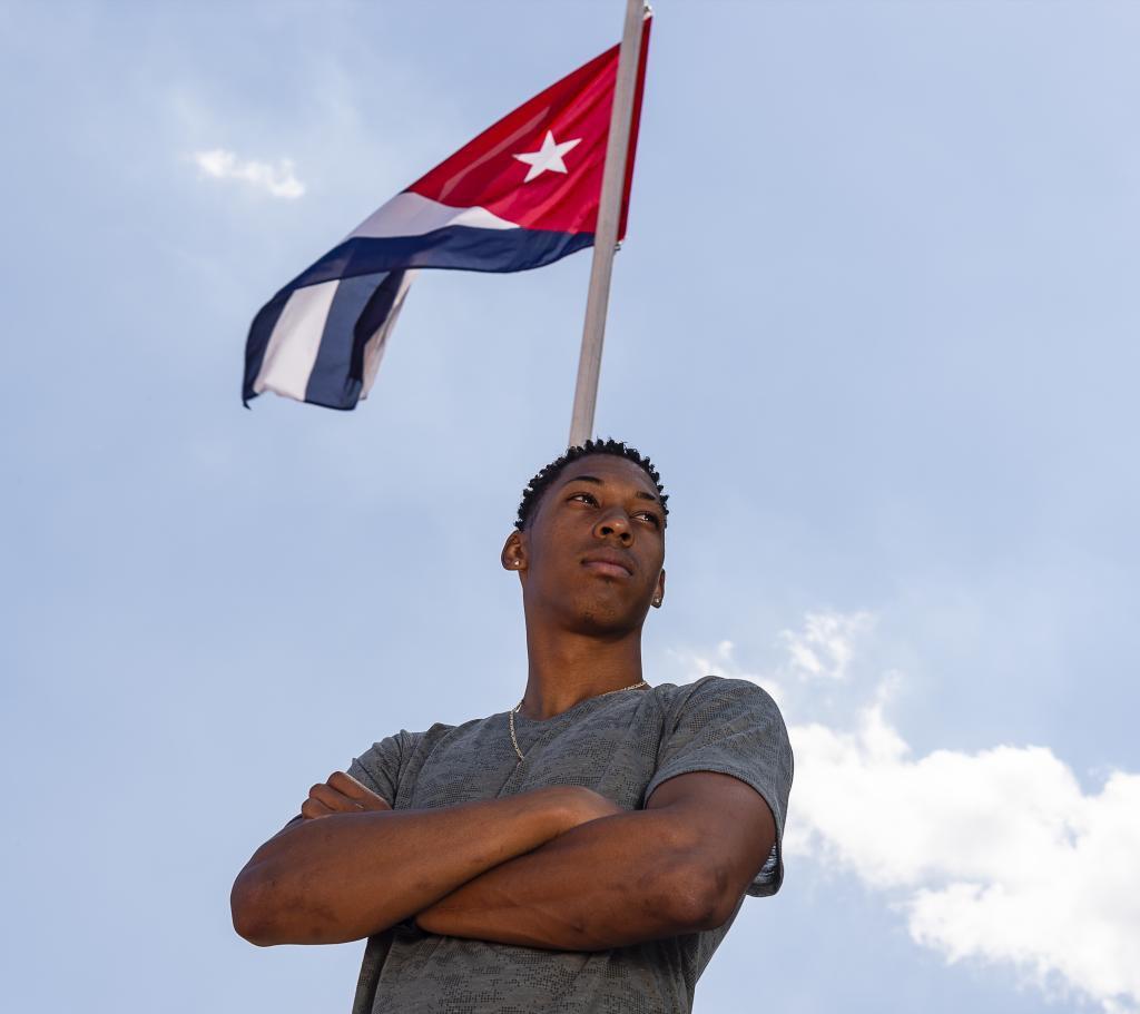 Echevarría posa delante de una bandera cubana en la pista de...