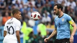 Godín disputa un balón con Mbappé.