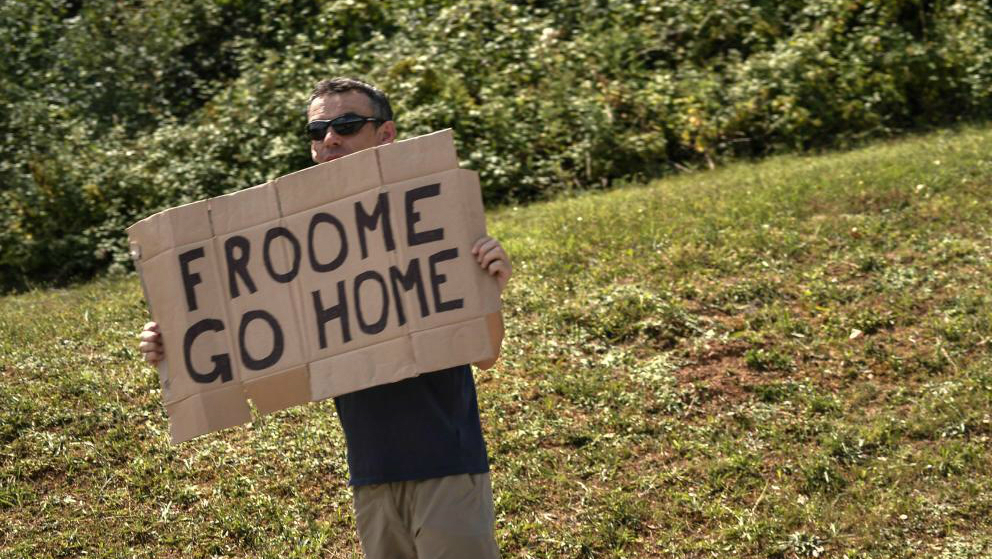 Un aficionado muestra una pancarta contra Froome durante la primera...