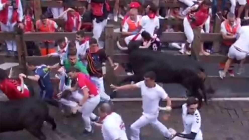 El toro golpea con su cuerno en la nuca a uno de los mozos....