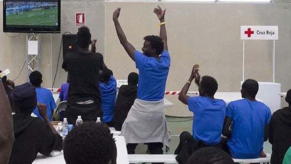 Migrantes del Aquarius siguen un partido del Mundial por televisión.