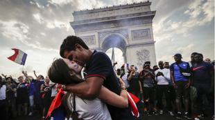Dos aficionados franceses se besan frente al Arco del Triunfo de...