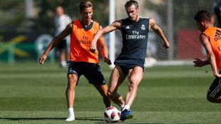 Bale, perseguido por Marcos Llorente, golpea el balón en el...