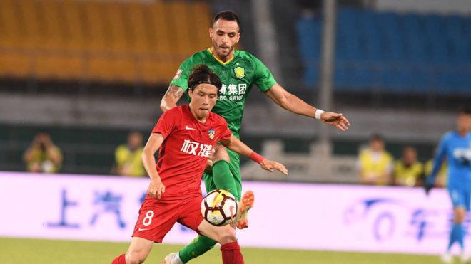 Zhang Xiuwei protege el balón ante Renato Augusto en el choque entre...