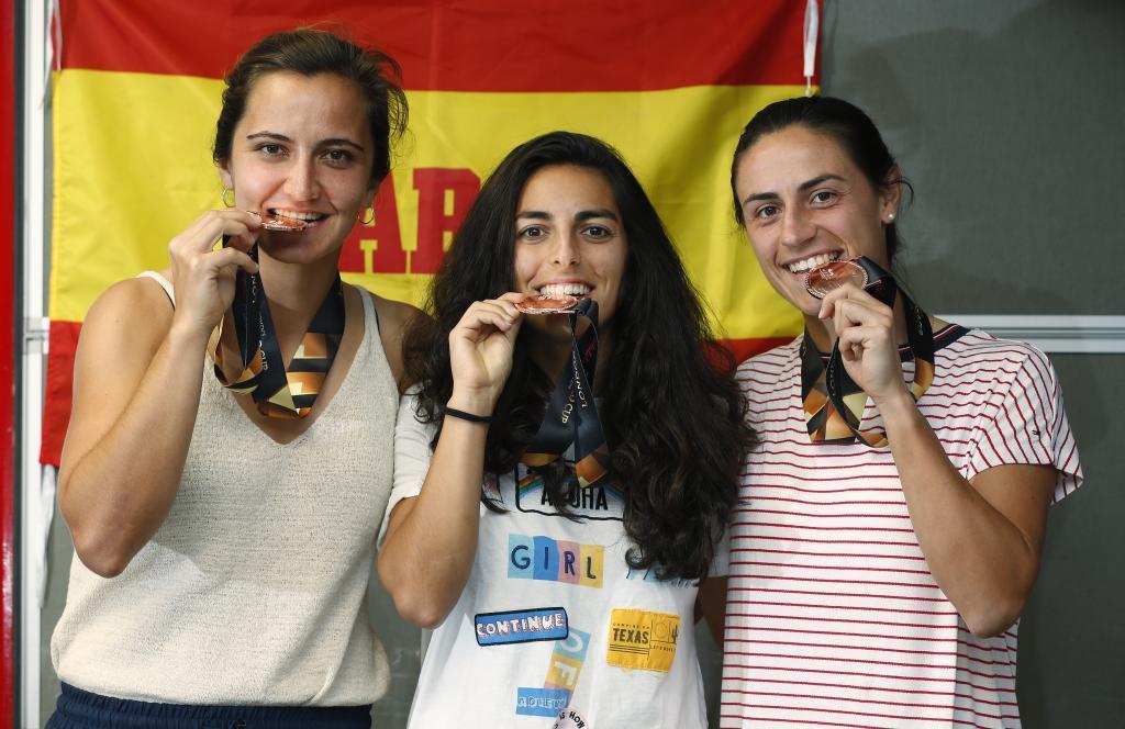 Lola Riera, Beatriz Pérez y Carmen Cano mordiendo la medalla.