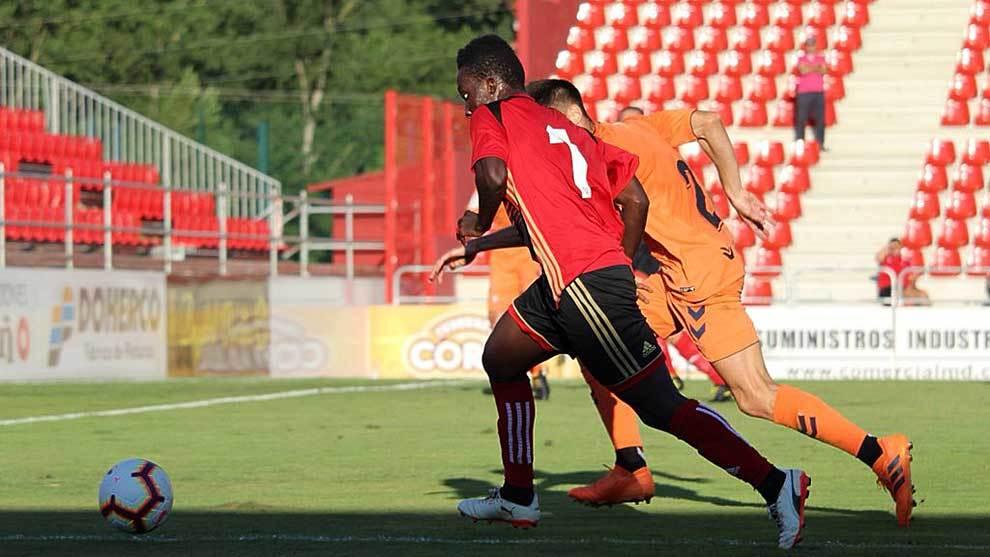 El local Carlos Julio se lleva el balón ante la defensa de un Osasuna...
