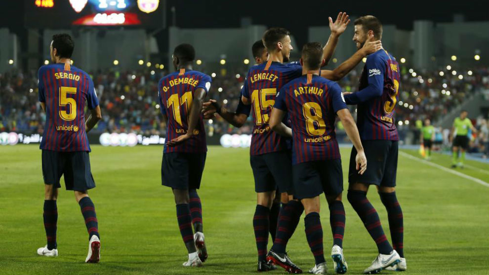 Pique celebrates with his teammates after scoring a goal during the...
