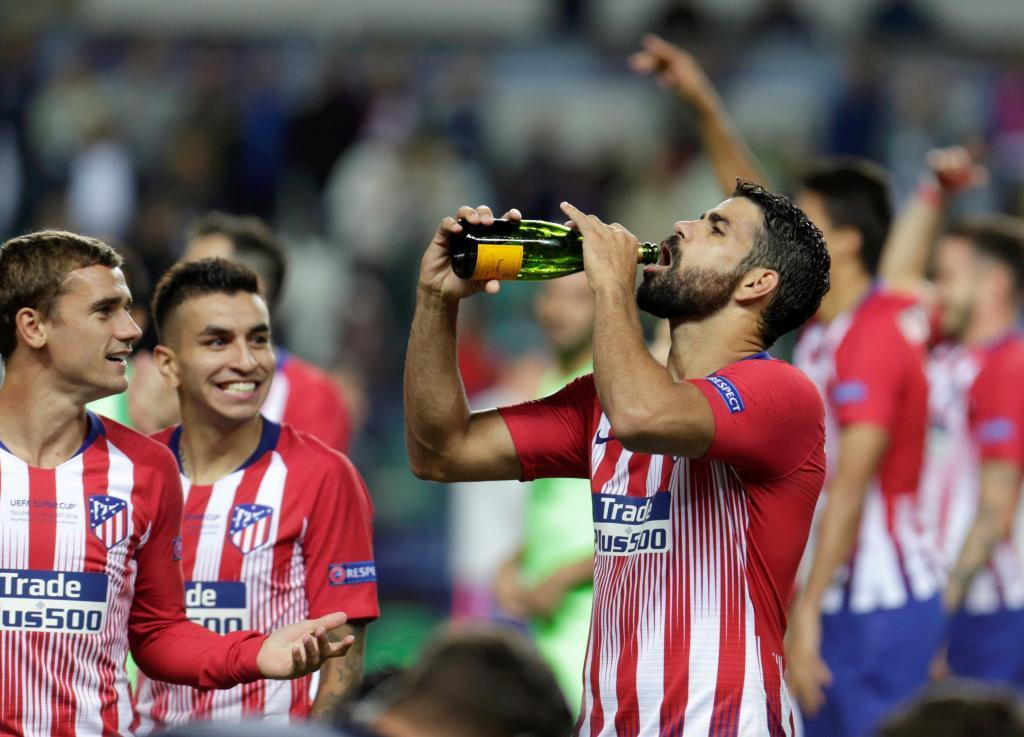 Costa celebrates the win with a bottle.