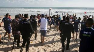 El surfista indonesio Hamish Daud porta la antorcha de los 18º Juegos...