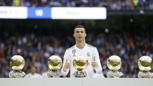 Cristiano posa con sus cinco Balones de Oro en el Santiago Bernabéu.