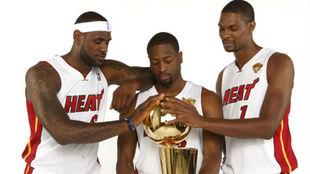 LeBron James, Dwyane Wade y Chris Bosh con uno de los campeonatos...