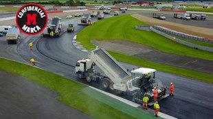 Operarios trabajan el asfalto de Silverstone.