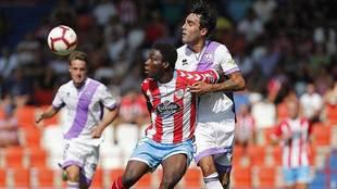 Dongou y Escassi disputan un balón durante el partido en el Anxo...