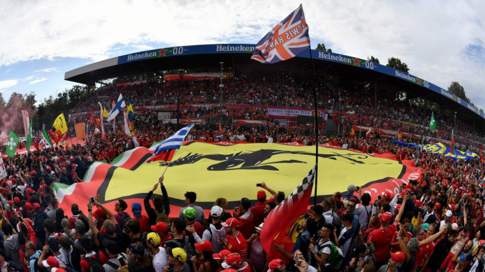 People hold a large banner with the logo of Scuderia Ferrari