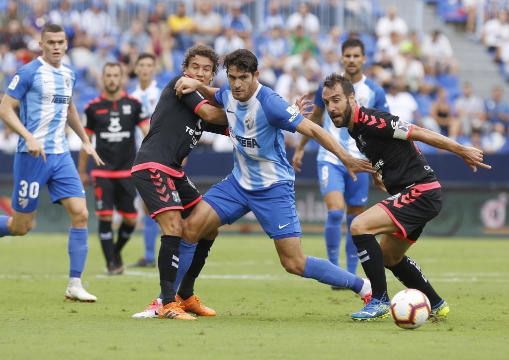 Blanco Leschuk controla el balón entre Milla y Carlos Ruiz