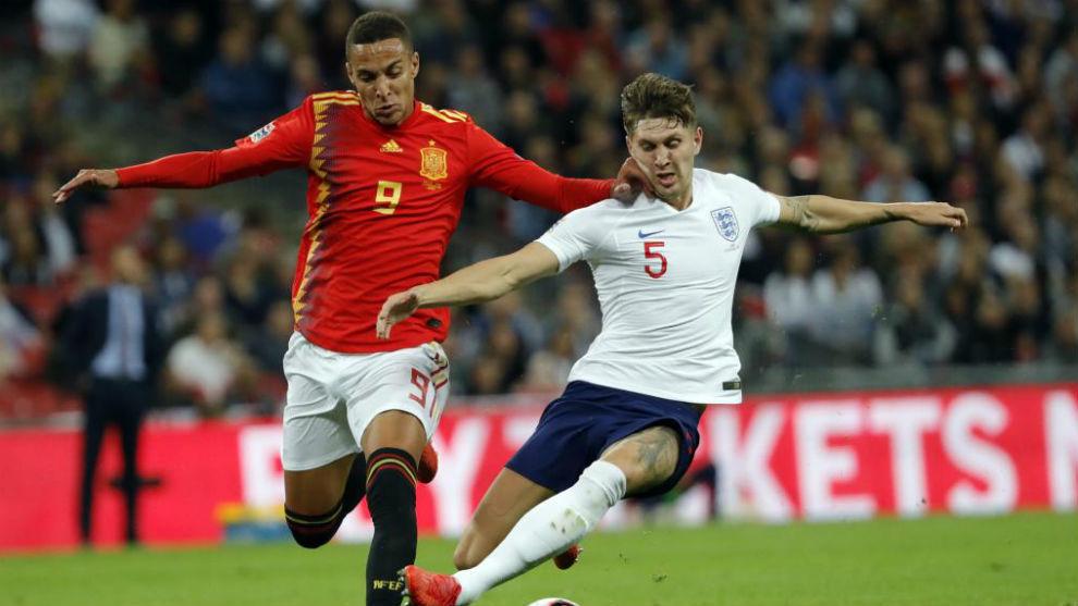 Spain's Rodrigo and England's John Stones vie for the ball.