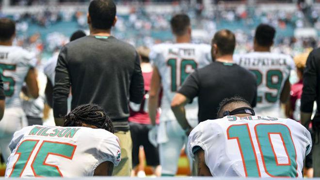 Kenny Stills y Albert Wilson, de los Dolphins, arrodillados durante el...