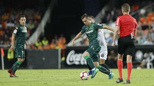 Lo Celso conduce un balón en Mestalla en presencia de Guardado.