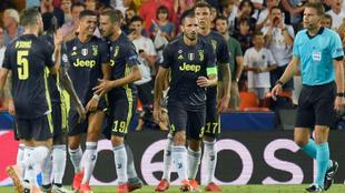Felix Brych, rodeado de jugadores de la Juventus tras la expulsión de...